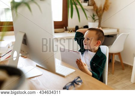 Schoolboy Study At Desk In His Room. Boy Use Laptop And Writing In Notebook. Books And Tablet On The