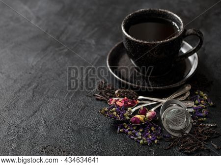 Tea Cup With Spoons And Various Tea On Black. Black And Green Loose Tea,rose Buds,blue Mallow Flower