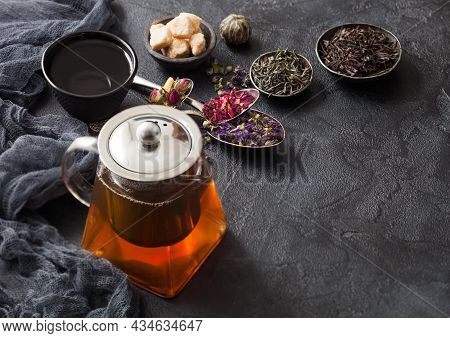 Glass Teapot With Spoons With Various Tea On Black. Rose Buds,blue Mallow Flowers,green And Black Lo