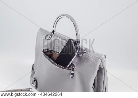 Smartphone In Open Pocket Of Bag On White Background.