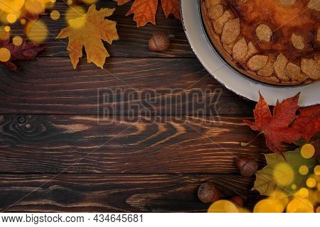 Autumn Background With Pumpkin Cake, Maple Leaves, Aples And Acorns. Top View. Copy Space
