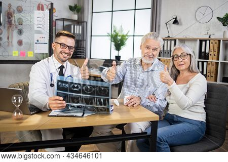 Mature Happy Couple Showing Thumbs Up, Visiting Their Doctor For Regular Check Up In Modern Clinic.