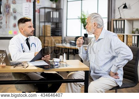 Competent Male Doctor Writing On Clipboard While Listening To Senior Patient At Private Office. Aged