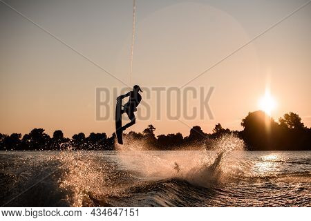 Great View Of Dark Silhouette Of Active Male Rider Holds Rope And Making Extreme Jump On Wakeboard A