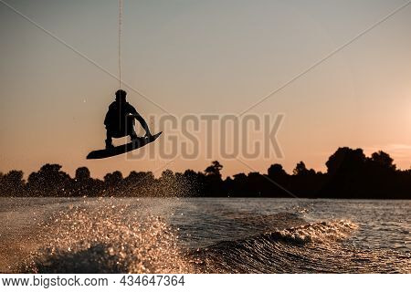 View Of Dark Silhouette Of Active Male Rider Holds Rope And Making Extreme Jump On Wakeboard At Suns