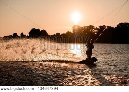 Great View Of Dark Silhouette Of Active Male Rider Holds Rope Riding On Wakeboard On Water Surface A