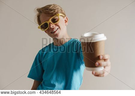 Portrait of a happy smiling casual preteen boy in t-shirt standing over isolated gray wall background holding takeayway coffee cup