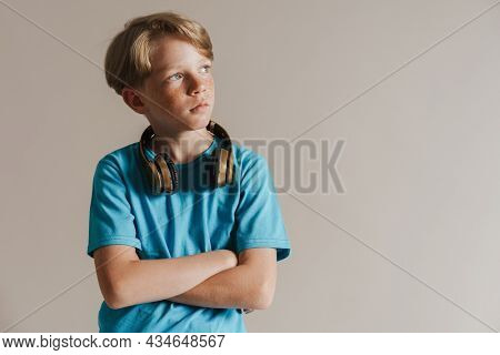Portrait of a casual preteen boy in t-shirt standing over isolated gray wall background listening to music with wireless headphones