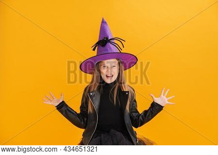 White girl wearing witch costume grimacing and gesturing isolated over yellow wall