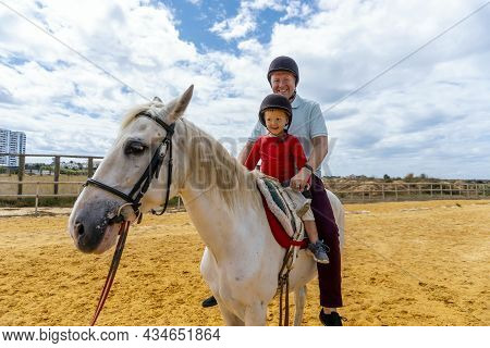 Father And Son Riding Horse In The Paddock