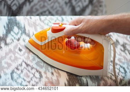 A Man Ironing Linen With An Electric Iron On An Ironing Board. Help Around The House.