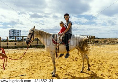 A Woman With Her 3 Years Old Son Sitting On The Horse In A Paddock