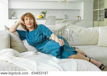Friendly Smiling Middle-aged Woman Resting. Woman In Blue Dress
