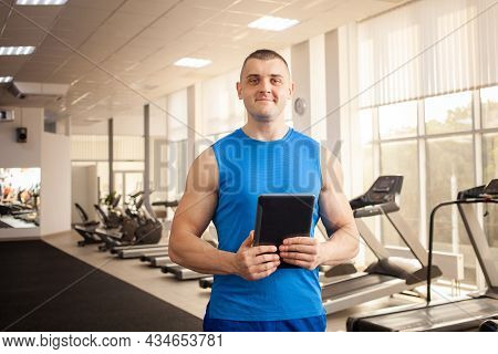 A Young Handsome Coach In The Process Of Working In The Gym. Sports Man With A Tablet. Coaching, Ind