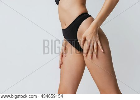 Beautiful Fitness Female Body, Legs Isolated On Gray Studio Background. Natural Beauty, Spa, Anti-ce