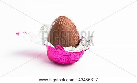 Easter egg unwrapped in pink foil on white background