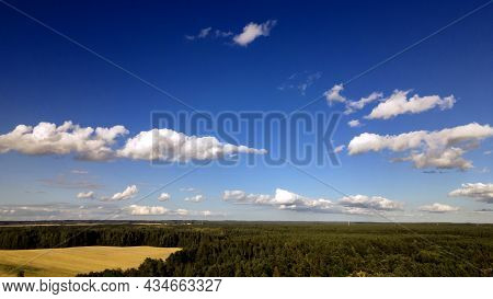 Top View Of Green Fields, Forest And Cloudy Blue Sky In Summer. Abstract Landscape With Lines Of Fie