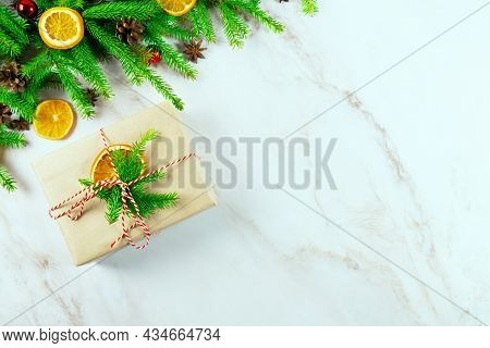 Branches Of A Christmas Tree With A Zero Waste Gift Box, Cones, Christmas Balls , Slices Of Orange A