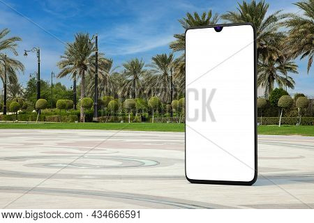 Big Modern Mobile Phone With Blank Screen As Template For Your Design In Empty City Street With Palm