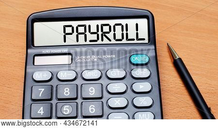 On A Wooden Table There Is A Black Pen And A Calculator With The Text Payroll. Business Concept