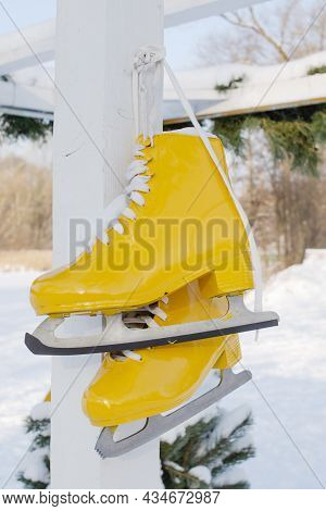Yellow Skates Hang On Background Of Snowy Nature. Sport And Healthy Lifestyle Concept.