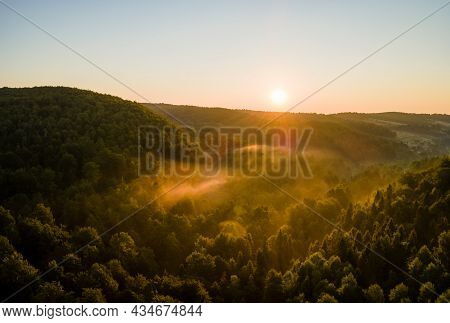 Vibrant Foggy Evening Over Dark Forest Trees At Bright Summer Sunset. Amazingl Scenery Of Wild Woodl