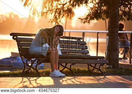 Lonely Unhappy Young Woman Sitting Alone On Park Bench On Warm Summer Evening. Solitude And Relaxing