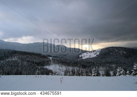 Gloomy Winter Landscape With Mountain Hills Covered With Evergreen Pine Forest After Heavy Snowfall