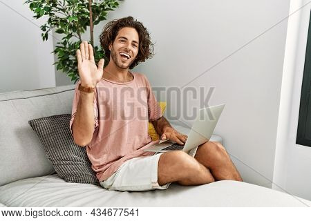 Young hispanic man sitting on the sofa at home using laptop waiving saying hello happy and smiling, friendly welcome gesture