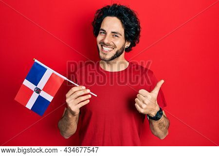 Handsome hispanic man holding dominican republic flag smiling happy and positive, thumb up doing excellent and approval sign