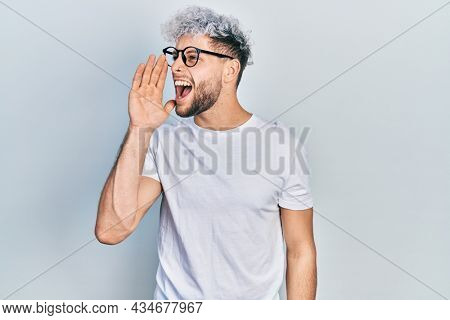 Young hispanic man with modern dyed hair wearing white t shirt and glasses shouting and screaming loud to side with hand on mouth. communication concept.