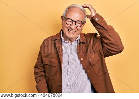 Senior man with grey hair wearing casual jacket and glasses confuse and wonder about question. uncertain with doubt, thinking with hand on head. pensive concept.