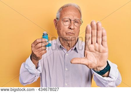 Senior man with grey hair holding medical asthma inhaler with open hand doing stop sign with serious and confident expression, defense gesture