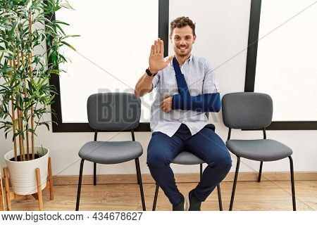Handsome young man sitting at doctor waiting room with arm injury waiving saying hello happy and smiling, friendly welcome gesture