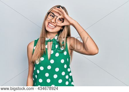 Beautiful hispanic woman wearing elegant shirt and glasses doing ok gesture with hand smiling, eye looking through fingers with happy face.