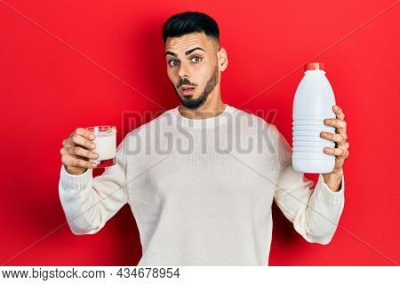 Young hispanic man with beard holding glass of milk and plastic bottle in shock face, looking skeptical and sarcastic, surprised with open mouth