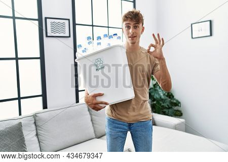 Young caucasian man holding wastebasket with recycling plastic bottles at home doing ok sign with fingers, smiling friendly gesturing excellent symbol