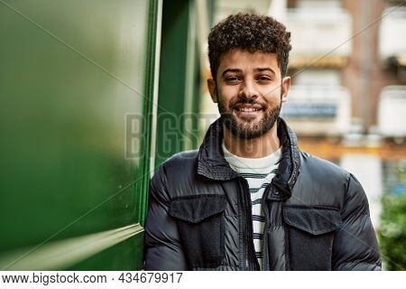 Young arab man smiling leaning on the wall