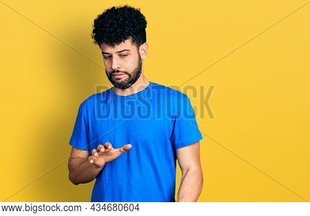 Young arab man with beard wearing casual blue t shirt disgusted expression, displeased and fearful doing disgust face because aversion reaction.