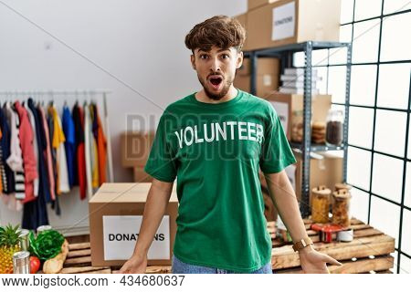 Young arab man wearing volunteer t shirt at donations stand in shock face, looking skeptical and sarcastic, surprised with open mouth