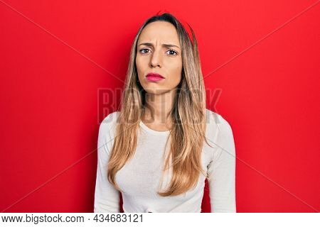 Beautiful hispanic woman wearing red diadem skeptic and nervous, frowning upset because of problem. negative person.