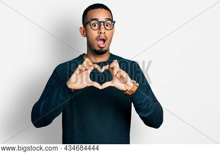 Young african american man doing heart symbol with hands afraid and shocked with surprise and amazed expression, fear and excited face.
