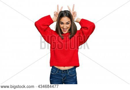 Beautiful brunette woman wearing casual winter sweater posing funny and crazy with fingers on head as bunny ears, smiling cheerful
