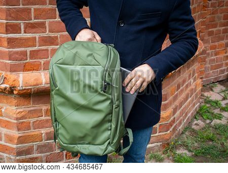 A Man Pulls A Laptop Out Of His Green Backpack. Universal City Sports Bag In Khaki Color. A Man's Ha