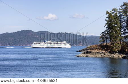 Salt Spring Island, British Columbia, Canada - August 23, 2021: Bc Ferries Passing By The Rocky Shor