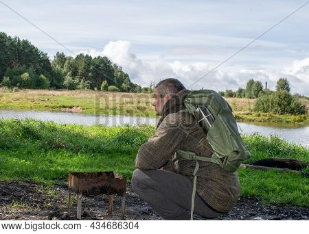 A Man With A Green Backpack And A Metal Thermos With Hot Tea Or Coffee Resting Near The Barbecue. To