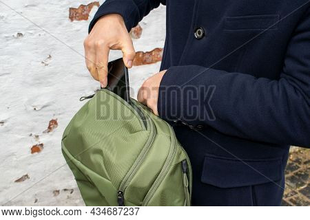 The Man's Hand Takes The Smartphone Out Of The Green Backpack. The Man Folds The Phone Into The Prot