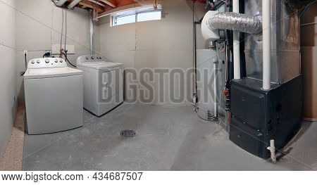 A Home Laundry Room With A Dryer, Washer, A High Efficiency Furnace With A Residential Gas Water Hea