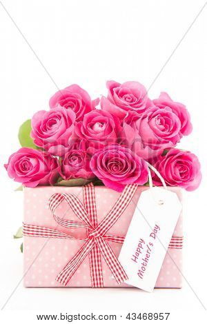Bouquet of beautiful pink roses next to a pink gift with a happy mothers day card on white background close up