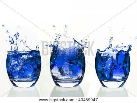 Serial arrangement of blue liquid splashing in tumbler on white background
